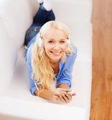 Vrouw met smartphone en hoofdtelefoon thuis — Stockfoto