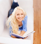 Smiling woman reading book and lying on couch — Stock Photo