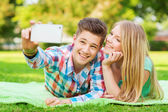 Smiling couple making selfie in park — Stock Photo