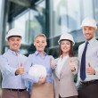 Happy business team in office showing thumbs up — Stock Photo #51687329