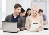 Two smiling students with laptop and tablet pc — Stock Photo