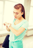 Surprised student girl looking at wristwatch — Stock Photo
