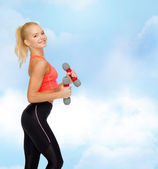 Smiling beautiful sporty woman with dumbbells — Photo