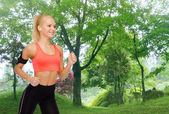 Sporty woman running with smartphone and earphones — Photo