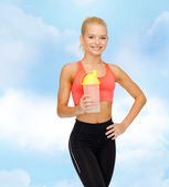 Smiling sporty woman with protein shake bottle — Stock Photo