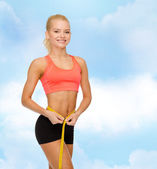 Smiling sporty woman with measuring tape — Stock Photo