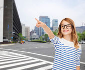 Cute little girl in eyeglasses pointing in the air — Foto de Stock
