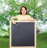 Happy little girl pointing finger to blackboard — Stock Photo