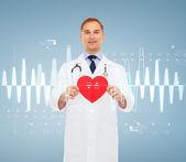 Lachende mannelijke arts met rood hart en stethoscoop — Stockfoto