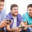 Smiling friends playing video games at home — Stock Photo #51692821
