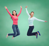 Smiling young women jumping in air — Stock Photo