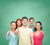 Group of smiling teenagers over green board — Stock Photo