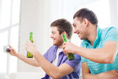 Smiling friends with smartphone and beer at home — Stock Photo