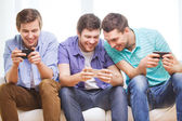 Smiling friends with smartphones at home — Stock Photo