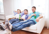 Happy male friends with beer watching tv at home — Stock Photo
