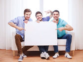 Happy male friends with blank white board at home — Stock Photo
