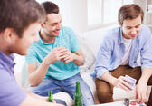 Smiling male friends playing cards at home — Stock Photo