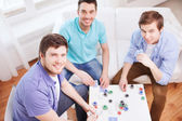 Three smiling male friends playing cards at home — Stock Photo