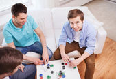 Three smiling male friends playing cards at home — Photo