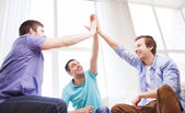 Smiling male friends giving high five at home — Stock Photo