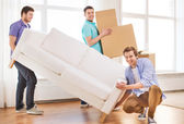Smiling friends with sofa and cardboard boxes — Stock Photo