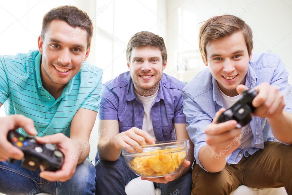 Sonrientes amigos jugando juegos de video en casa foto - Juegos para 3 personas en casa ...