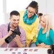Smiling team with photocamera working in office — Stock Photo #51783693