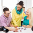 Smiling team with printed photos working in office — Stock Photo #51783701