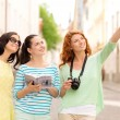 Smiling teenage girls with city guide and camera — Stock Photo #51785491
