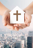 Close up of hands and paper house with cross — Stock Photo