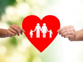 Closeup of hands holding red heart with family — Stock Photo