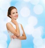 Smiling woman in white dress wearing diamond ring — Stock Photo