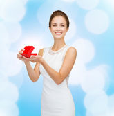 Smiling woman holding red gift box — Stock Photo