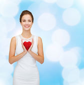 Smiling woman in white dress with red heart — Stock Photo