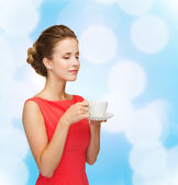 Smiling woman in red dress with cup of coffee — Foto de Stock