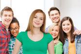 Group of smiling teenagers over classroom — Stock Photo