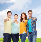 Group of smiling teenagers over blue sky and grass — Stock Photo