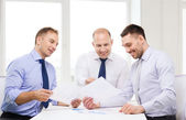 Smiling businessmen with papers in office — Stock Photo
