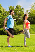 Smiling couple stretching outdoors — Stock Photo
