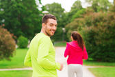 Smiling couple running outdoors — Стоковое фото