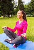 Smiling woman meditating sitting on mat outdoors — Stock Photo