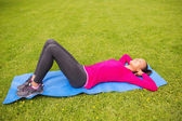 Smiling woman doing exercises on mat outdoors — Stock Photo