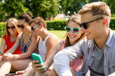 Smiling friends with smartphone making selfie — Foto de Stock