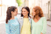 Smiling teenage girls with on street — Stock Photo