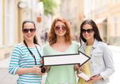 Smiling teenage girls with white arrow outdoors — Stock Photo