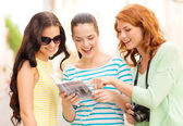 Smiling teenage girls with city guide and camera — Stock Photo