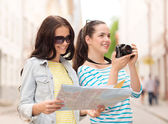 Smiling teenage girls with map — Stock Photo