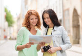 Smiling teenage girls with map and camera — Stock Photo