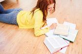 Smiling teenage girl reading books on floor — Stock Photo