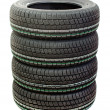 Four new tires stacked on white background - Photo